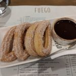churros with chocolate sauce resting on a restaurant menu